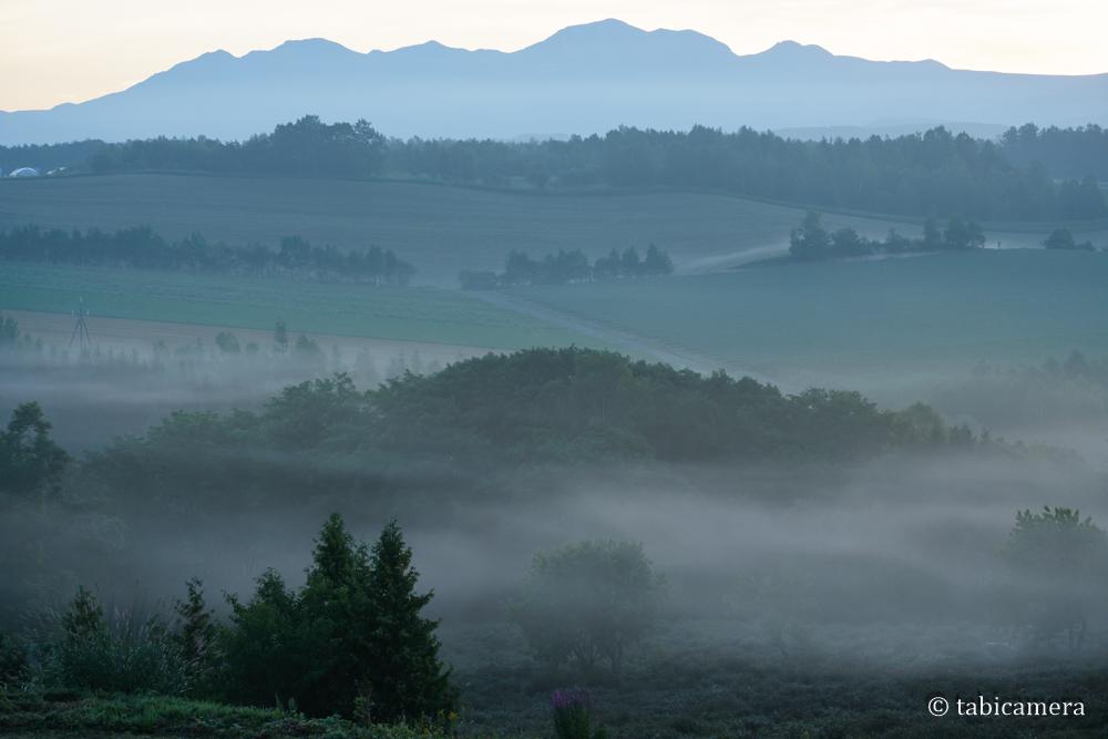 朝霧に包まれる深山峠と十勝岳
